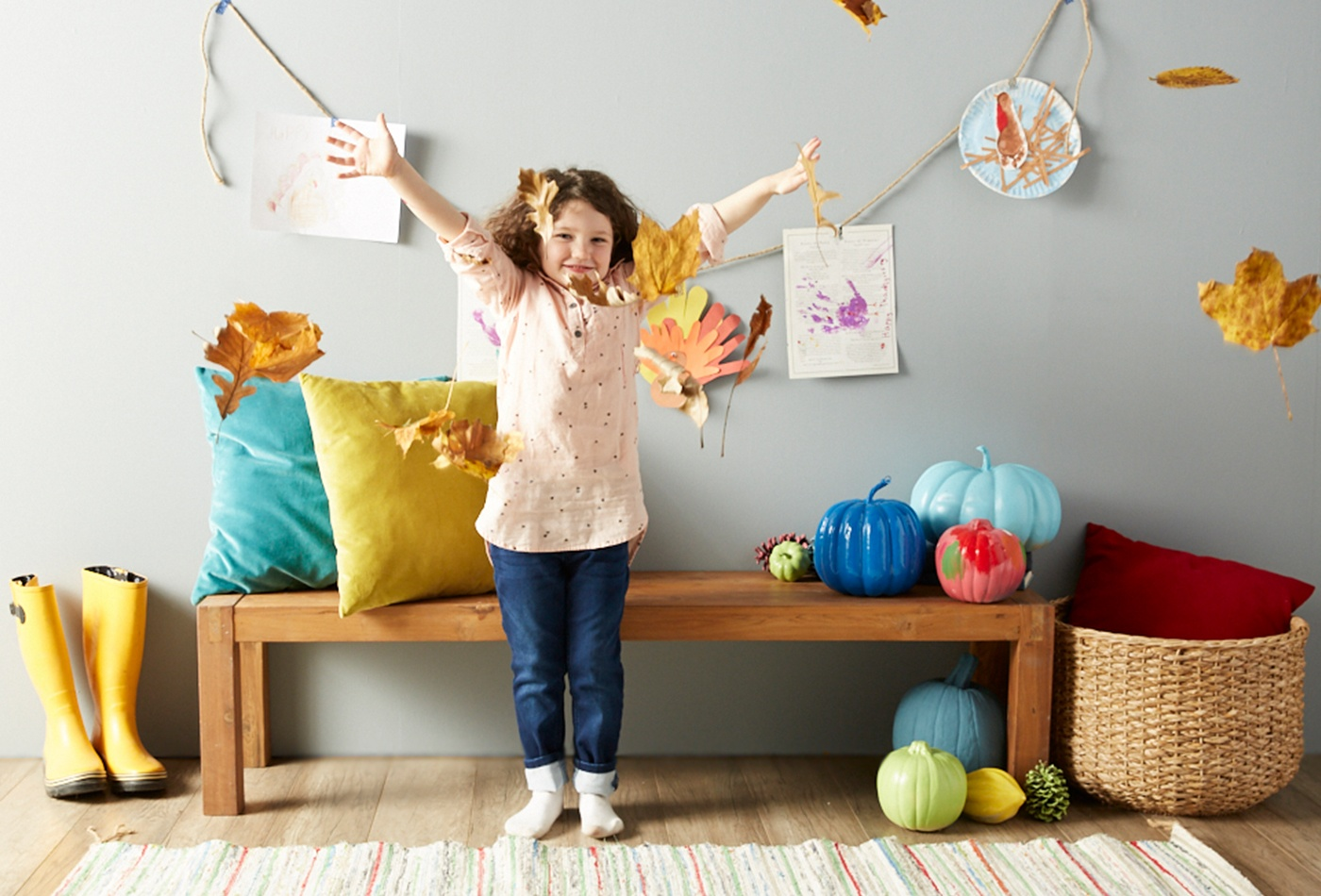 child-throwing-leaves-in-thanksgiving-decorated-home