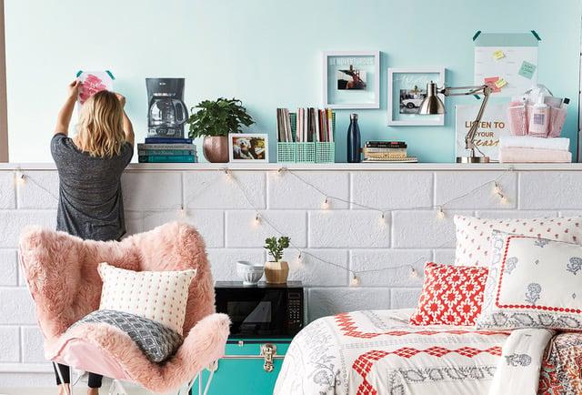 stylist-hanging-artwork-college-dorm-room